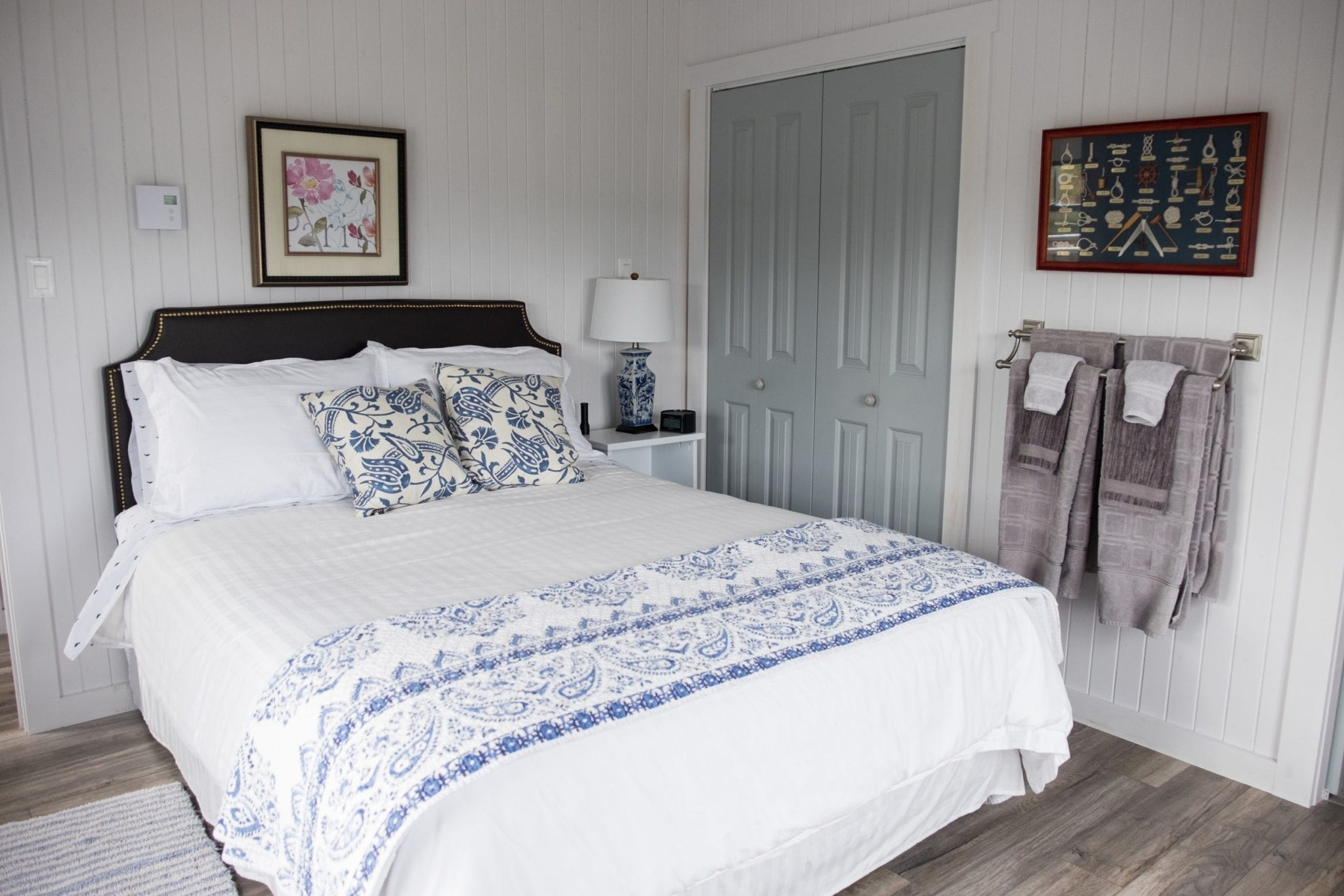 A white queen bed in a white and blue-decorated bedroom at the Artisan Inn.