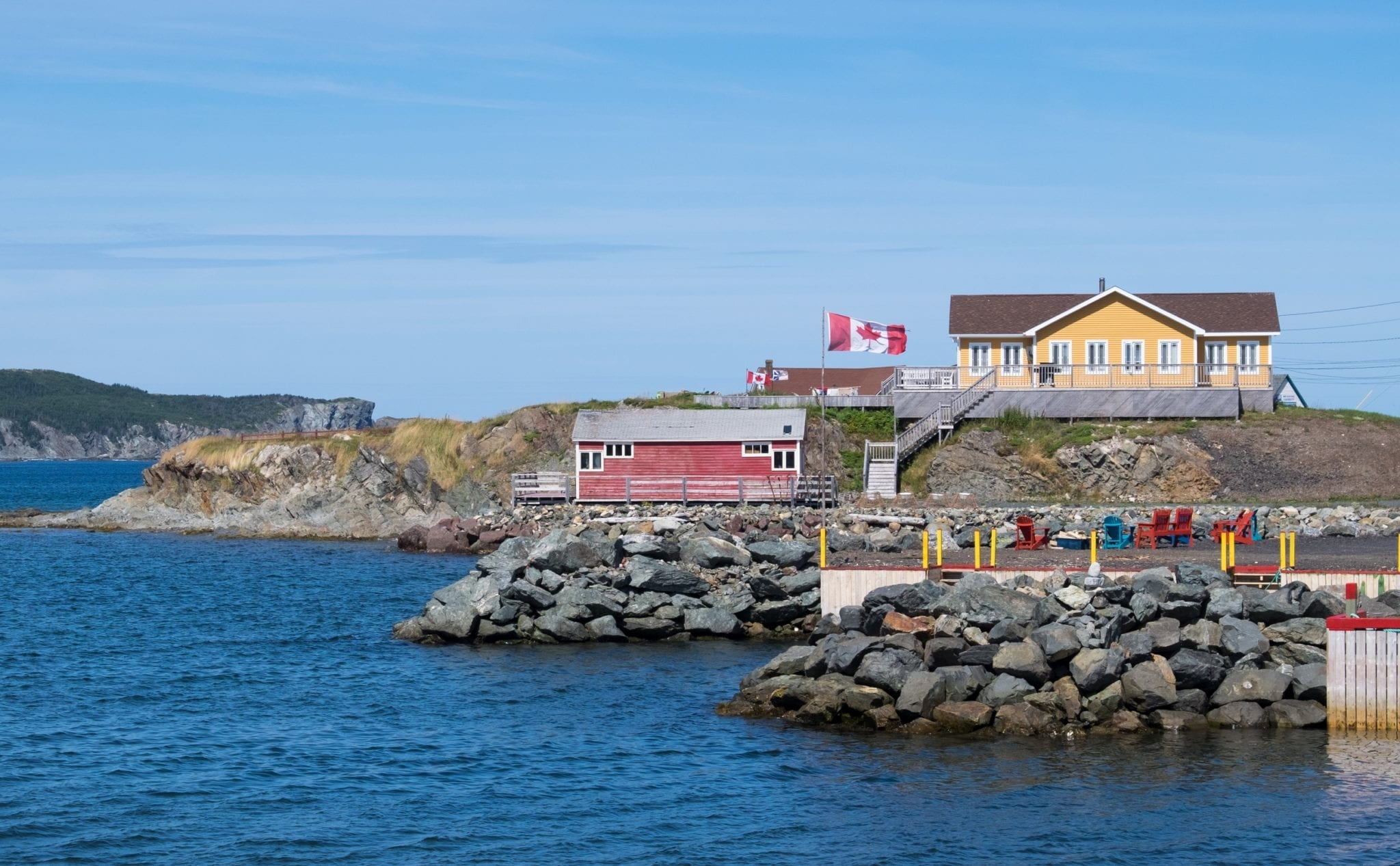 Red and yellow cottages on the water's edge, a Canadian flag flying.