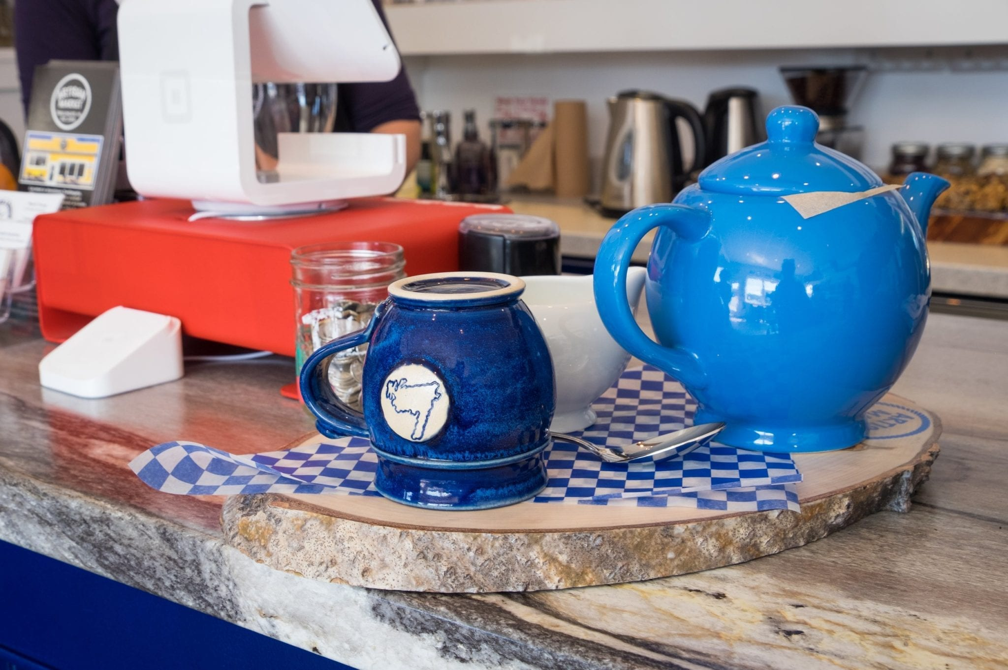 A bright blue teapot and dark blue teacup with the outline of Newfoundland on it, served on a slab of wood.