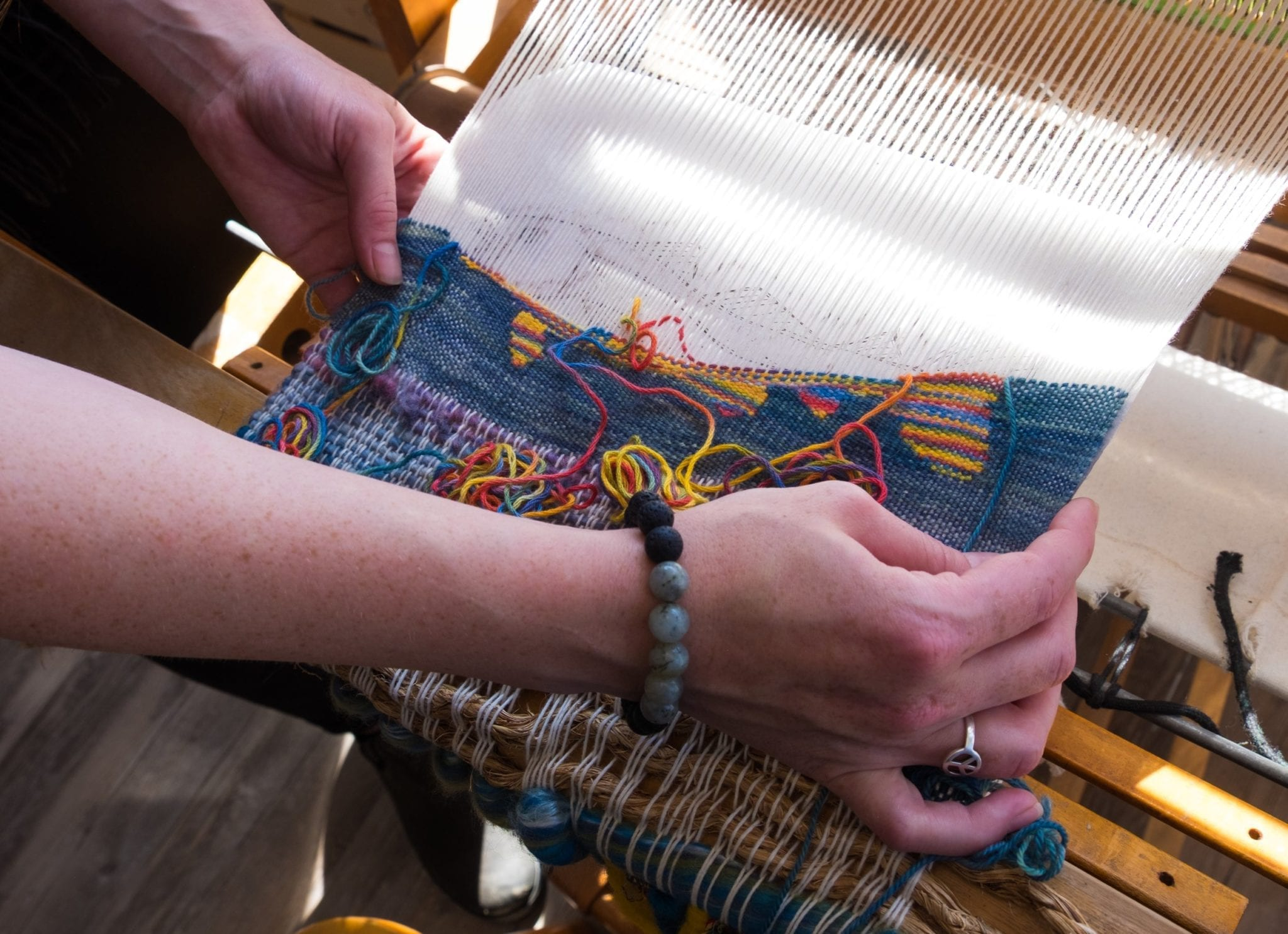 Hands holding up a partially woven fabric fish on a loom in Twillingate.