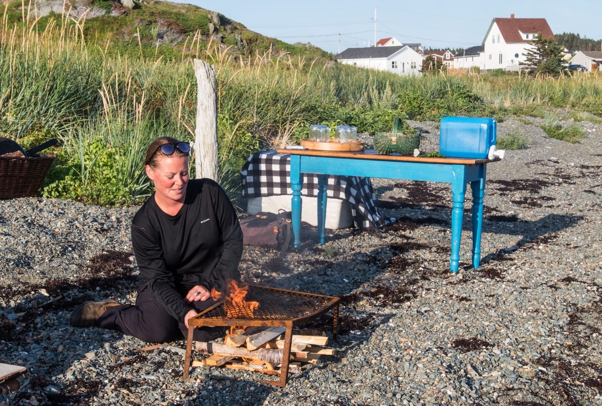 Chef Crystal tends a campfire on the beach, with cottages in the background.