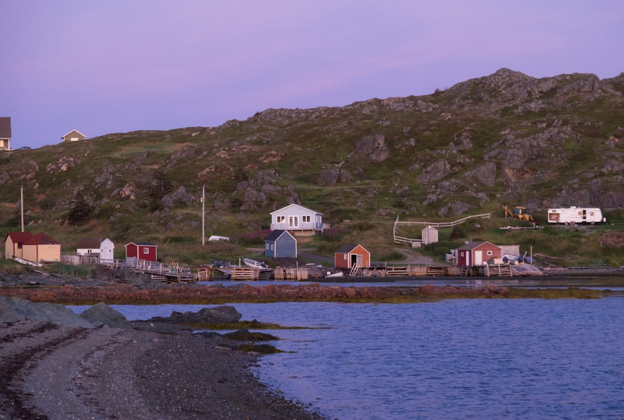 Cottages on the beach in Twillingate at dusk, the sky light purple, the cliffs bright green.