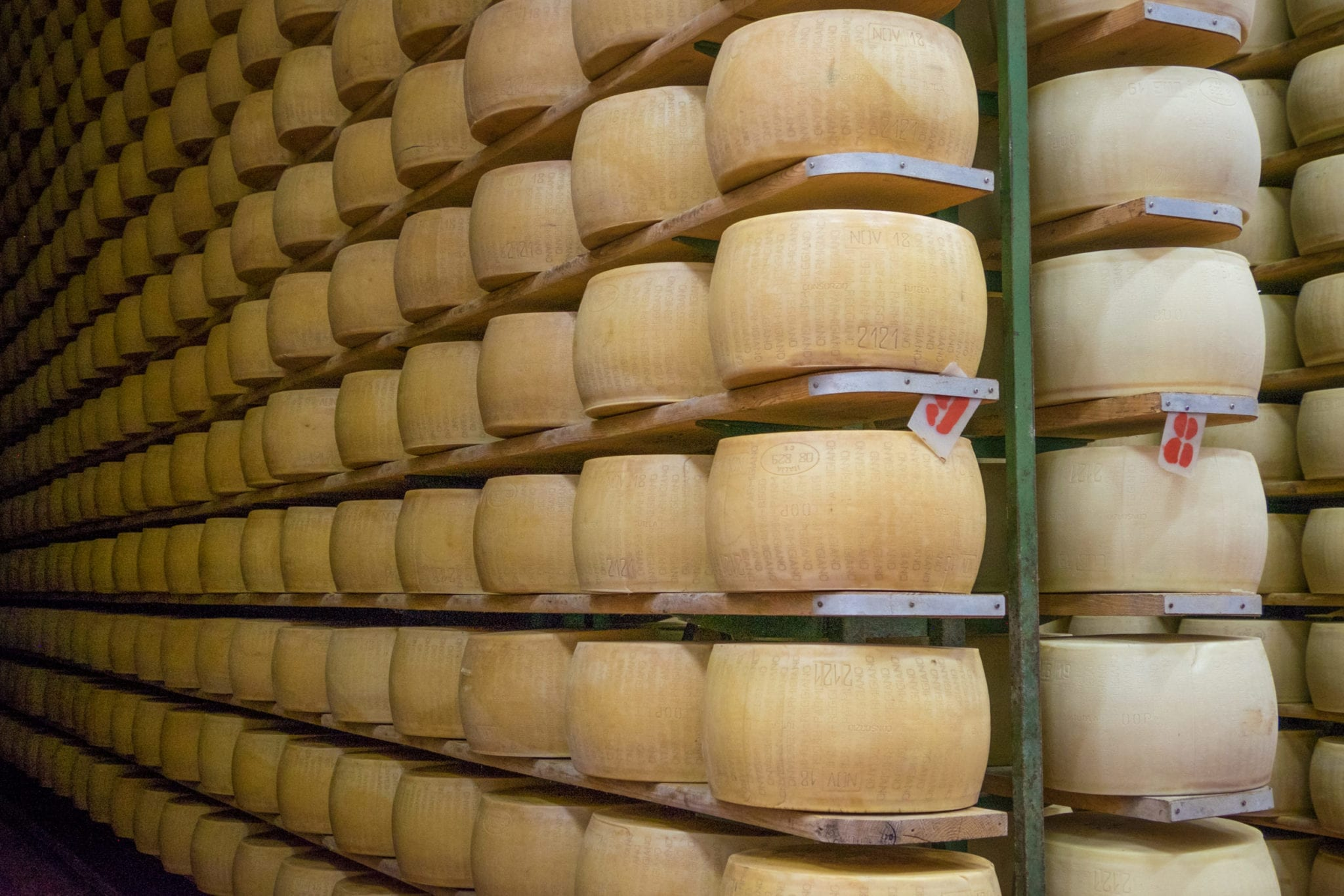 Rows and stacks of Parmigiano Reggiano wheels on shelves.