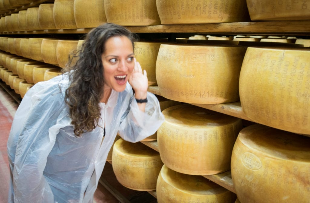 Kate leans into the rows of cheese and holds her hand to her ear like she's listening to them.