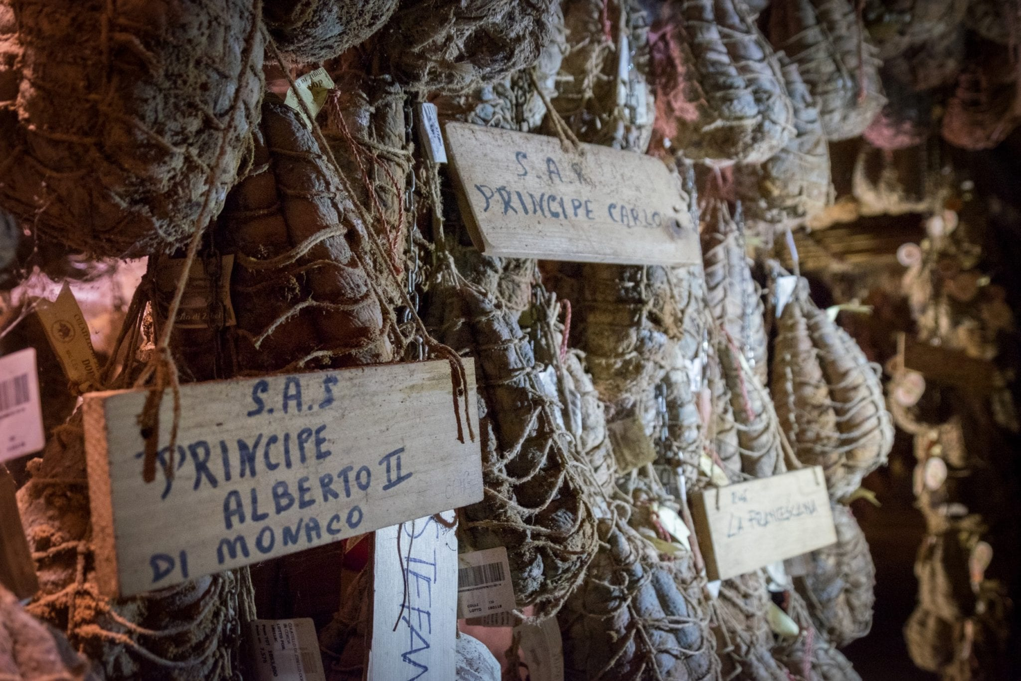 "Hanging culatello in the basement, some labeled with ""Principe Alberto II"" and ""Principe Carlo"" for Prince Albert and Prince Charles."