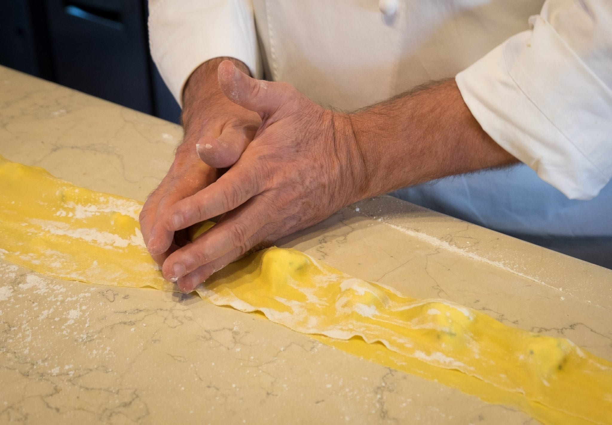 Chef's hands sculpting tortelli -- large tortellini. His hands surround the cheese stuffing and push down.