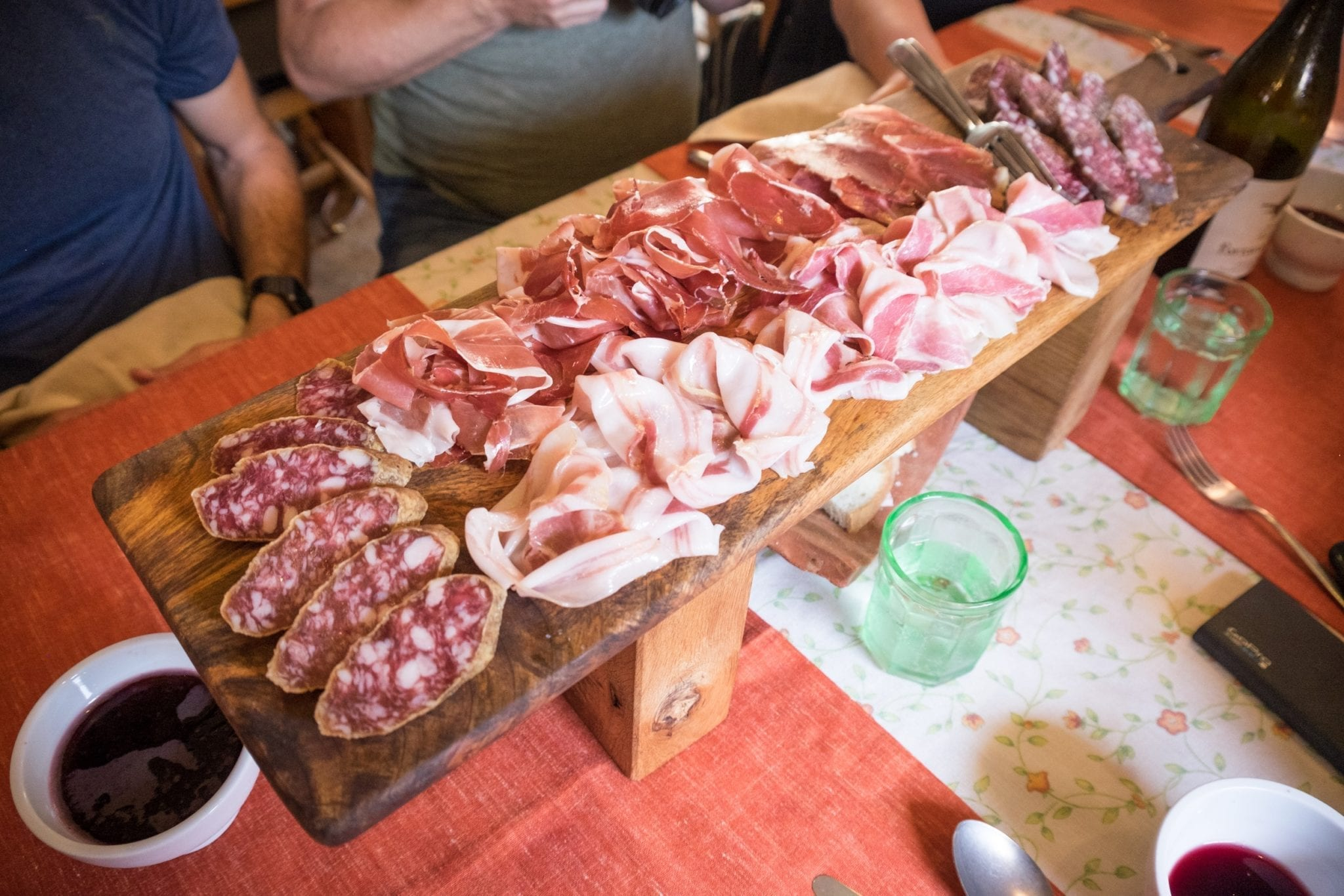 A large wooden platter covered with several cured meats, including culatello, salami, and raw pancetta (white and slithery and gross, but hey, some people are into that).