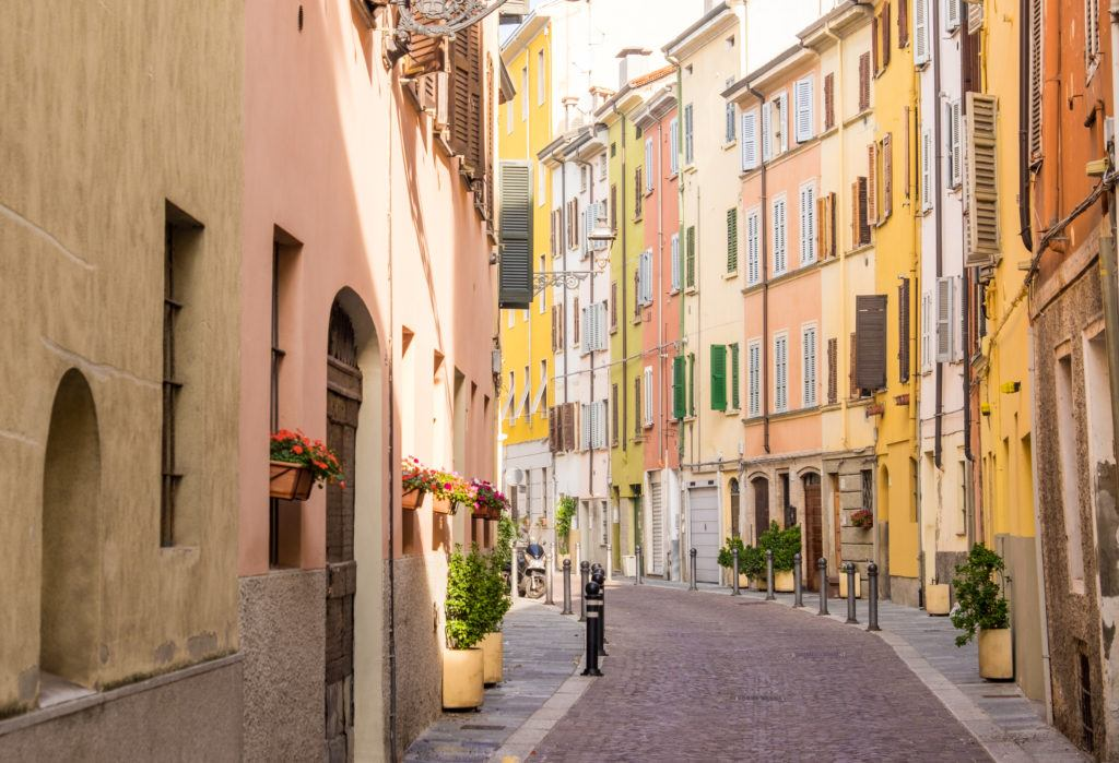 A colorful street in Parma with yellow, pale red, and orange buildings stacked together, each with green shutters.