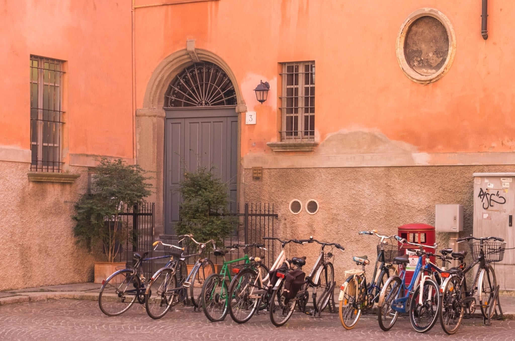 Several bicycles parked outside a building with a bright pink wall and a large gray-blue door.