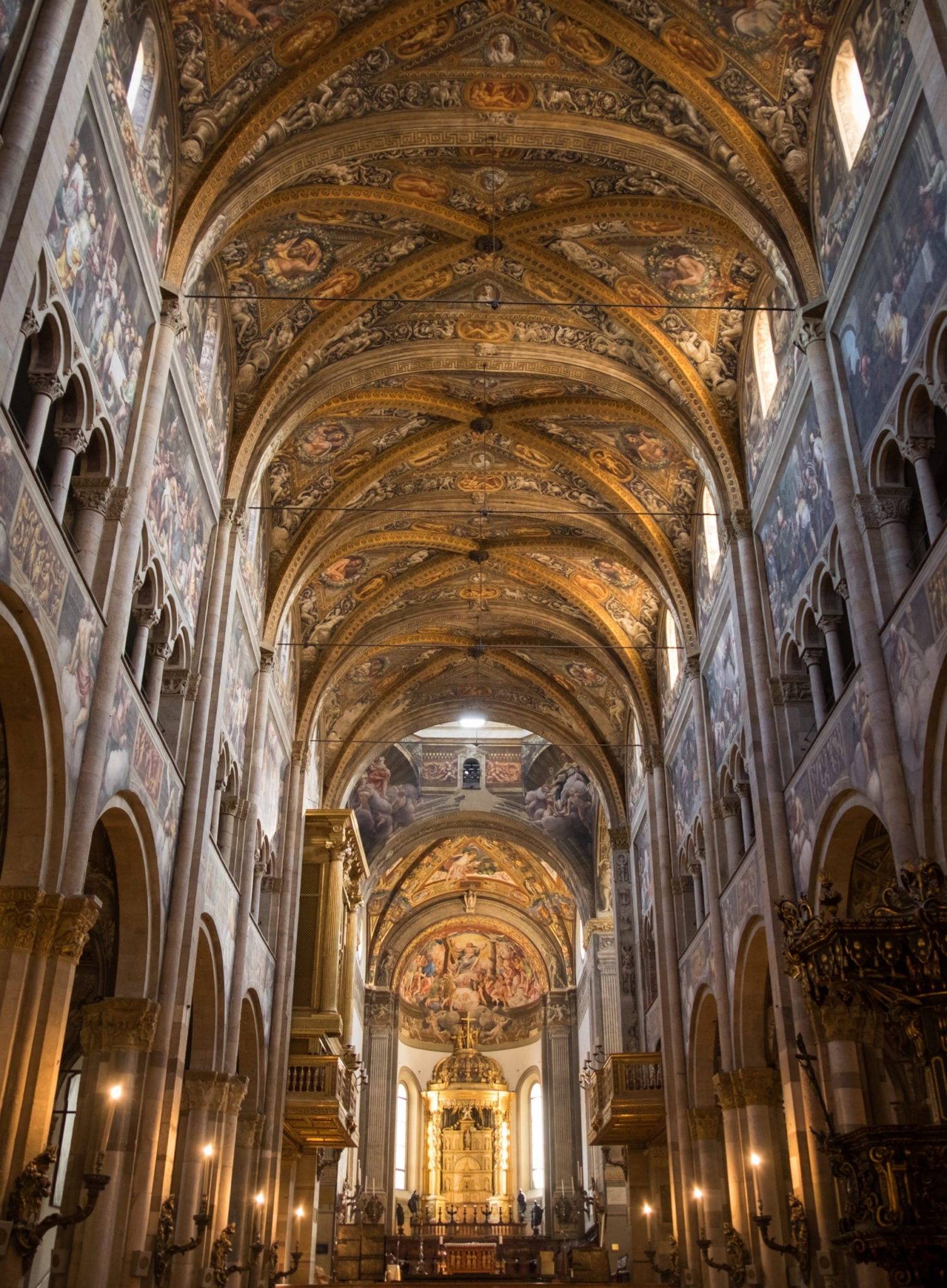 Parma's cathedral, leading back to the altar, each wall covered with paintings and ornate gold decoration.