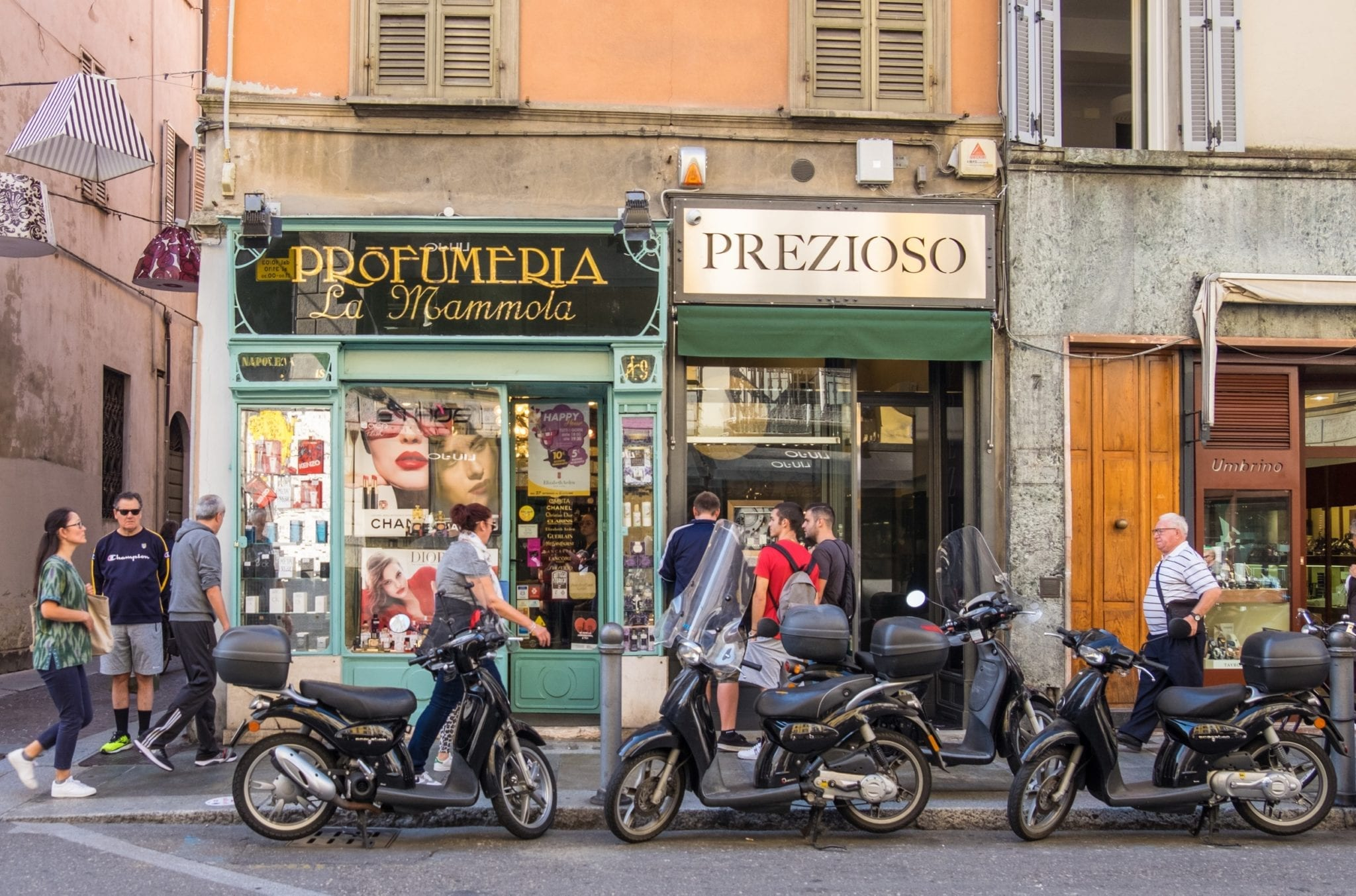 Old-fashioned stores painted green side by side in Parma, Italy, with motorbikes parked in front and people walking by.
