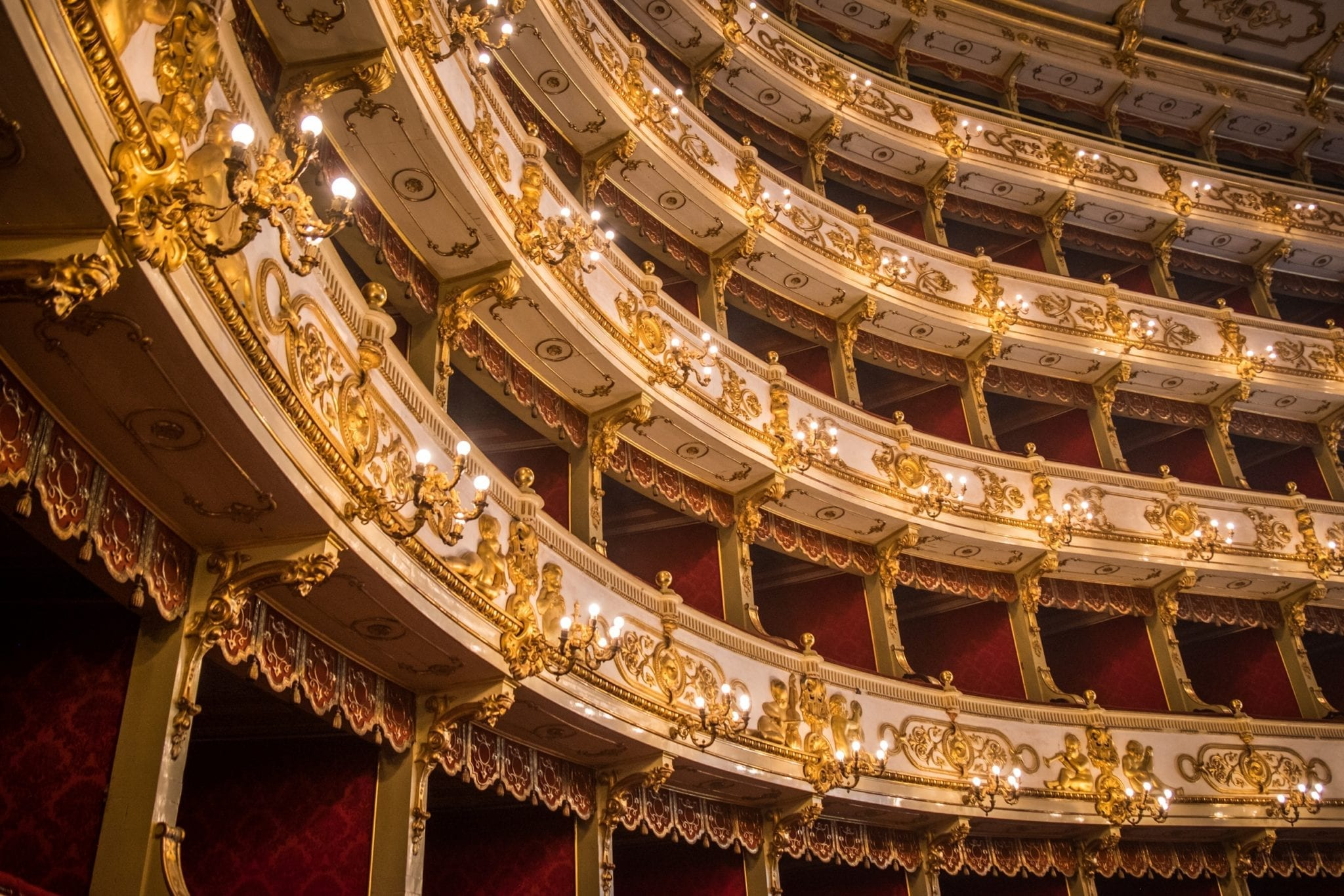 The ornate theater with stacked rows of gold-and-white balconies.