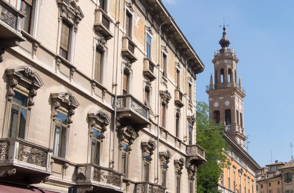 A view of Parma's crenellating side buildings with a steeple in the distance.