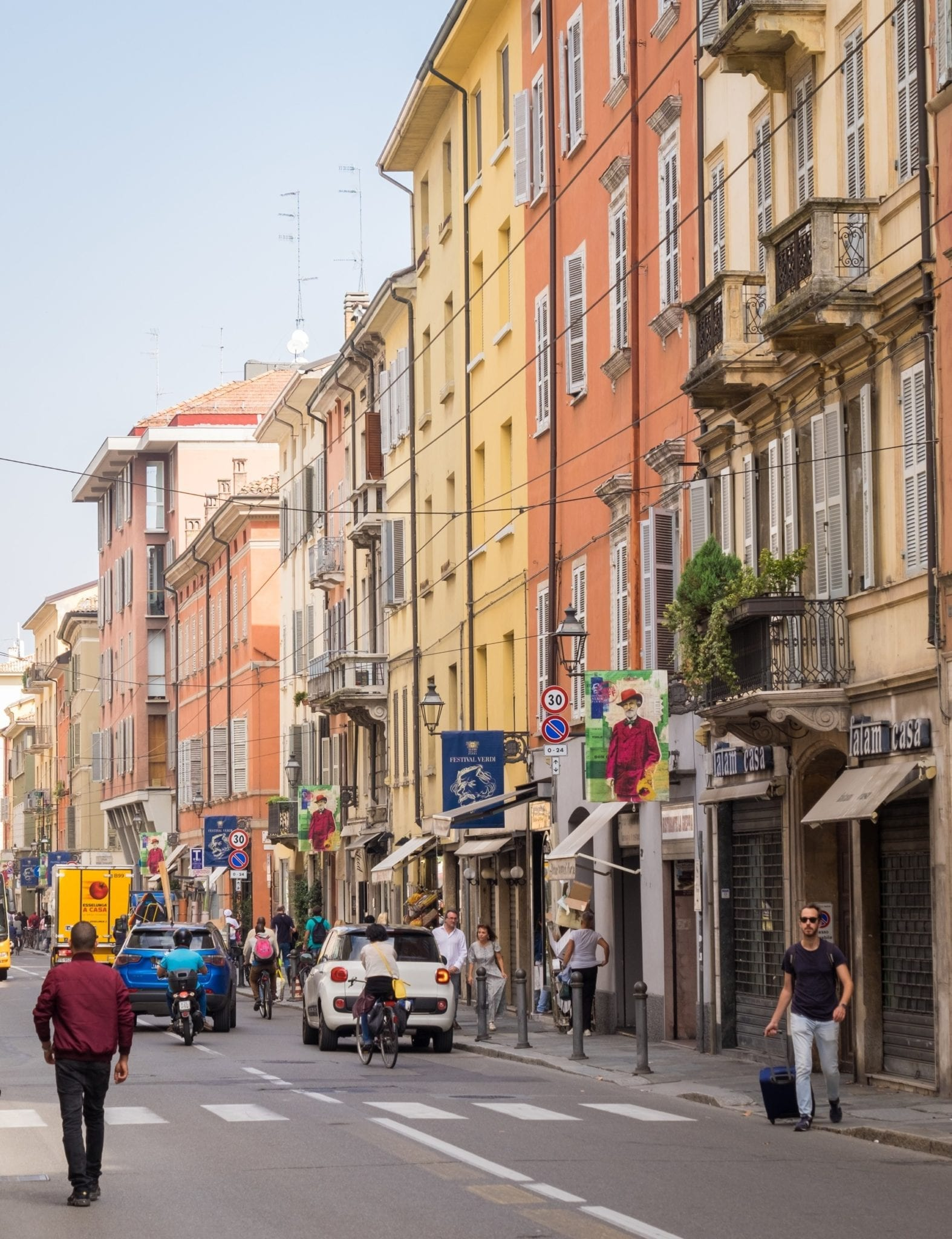 People walking down the streets surrounded by warm-colored buildings in Parma, Italy.