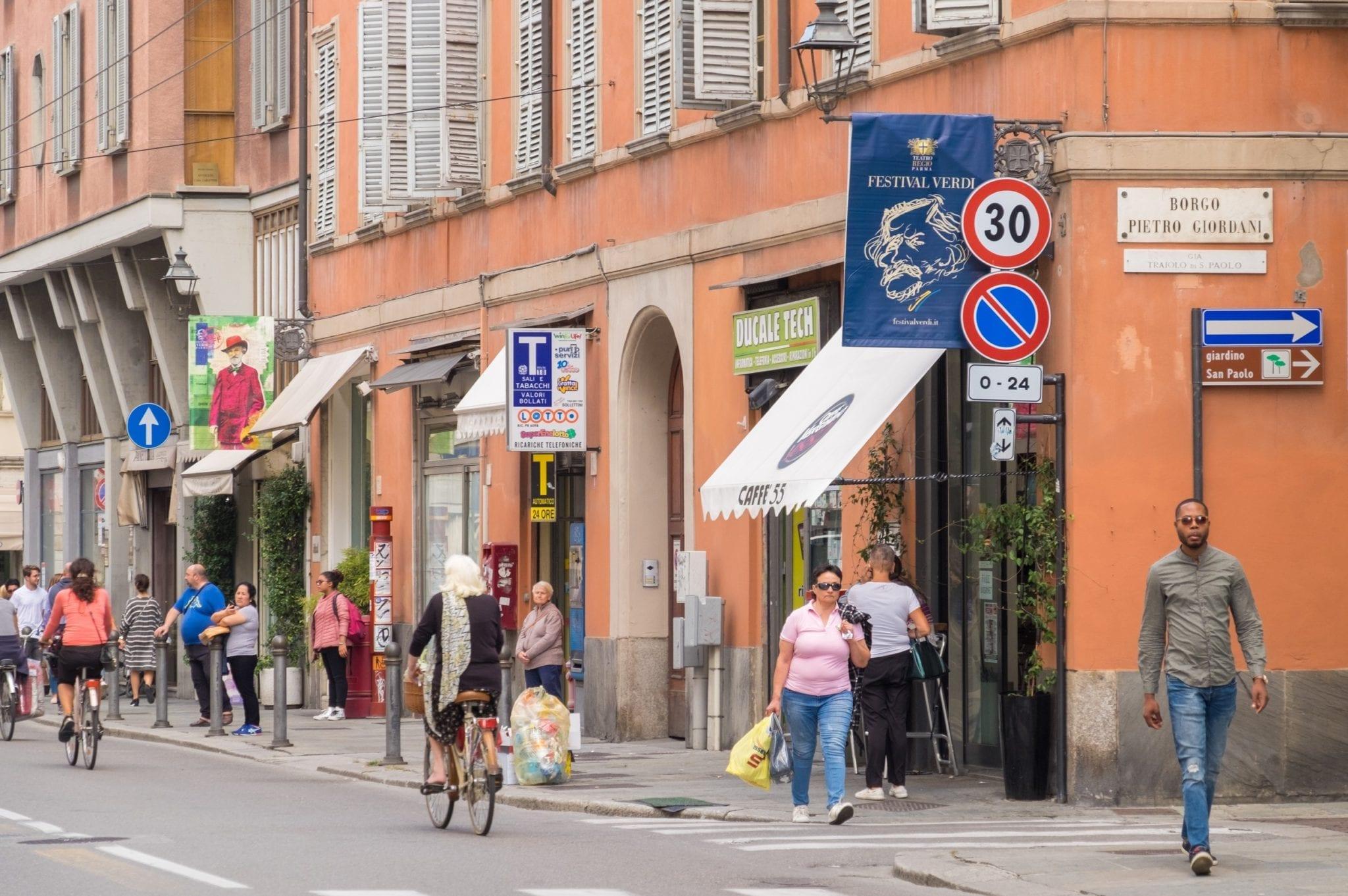 People walking down the street in front of orange buildings in Parma.