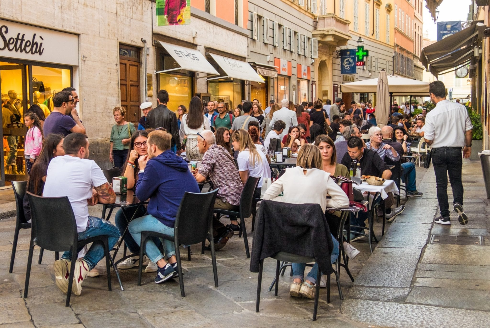 People sitting outside at a restaurant in Parma, Italy
