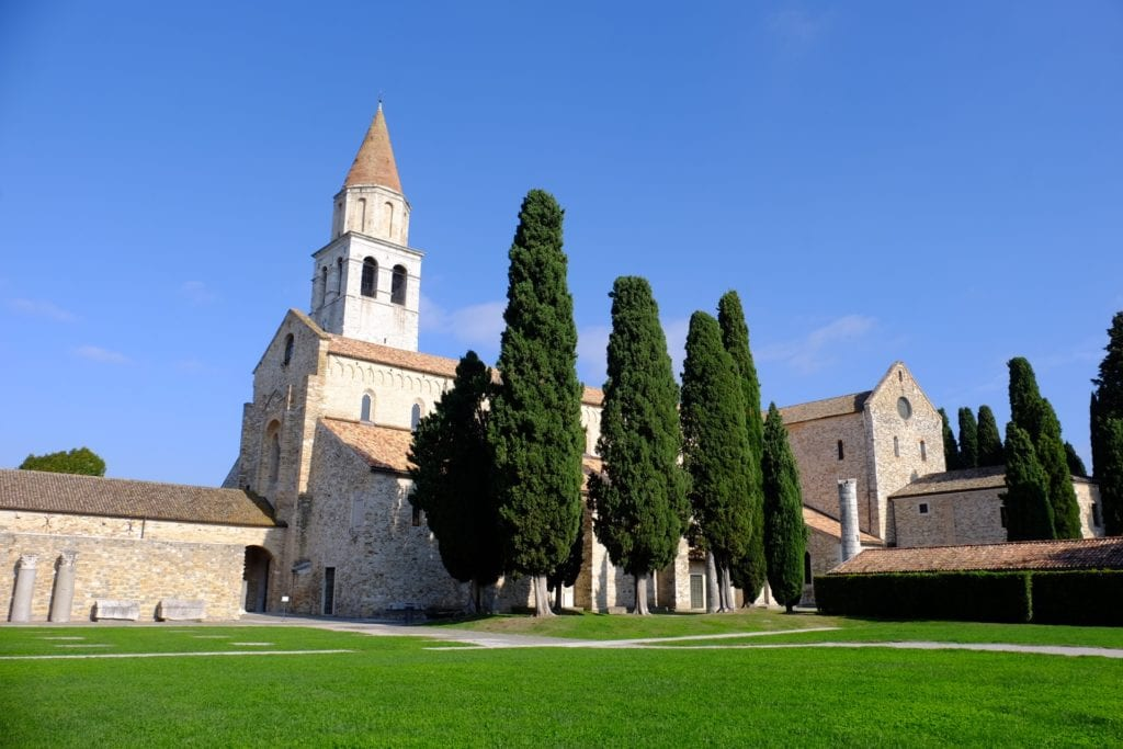 The cathedral in Aquileia, Italy, a small church with an orange roof with tall cypress trees in front.