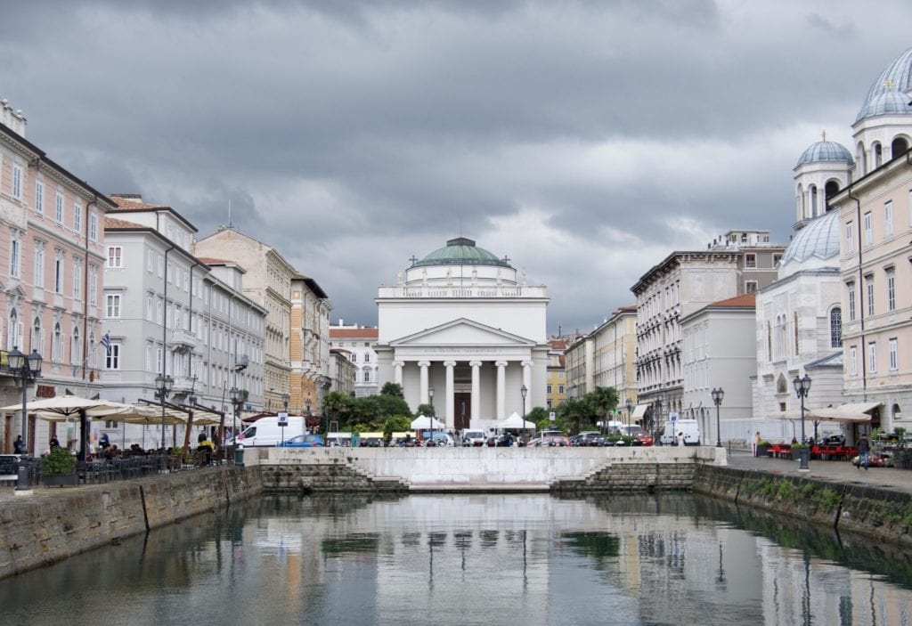 A white building with columns behind a canal, underneath a cloudy gray sky in Trieste, Italy.