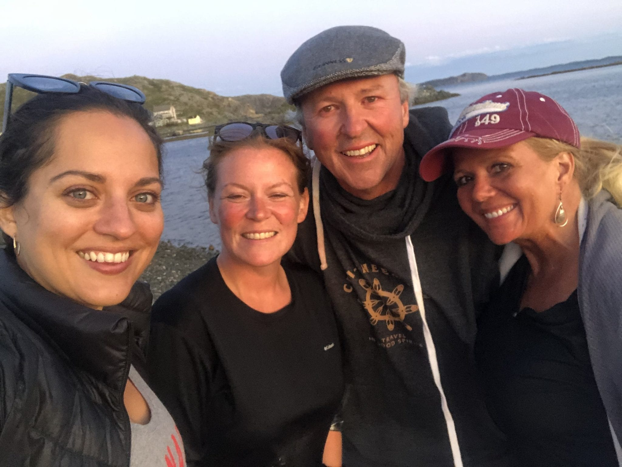 Kate and her three new friends pose for a smiling selfie on the beach.