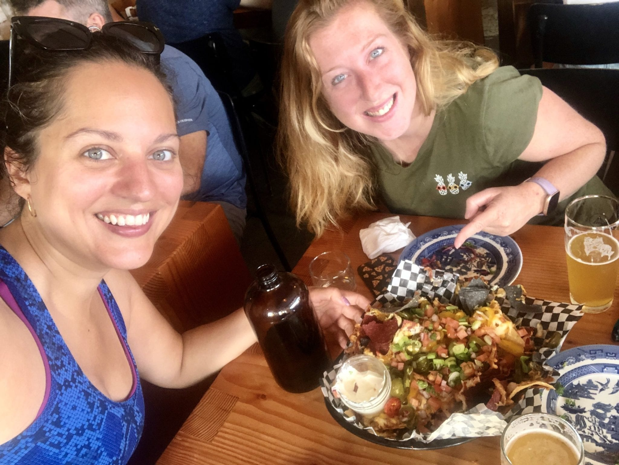 Kate and Candice pose for a selfie with beers and nachos.