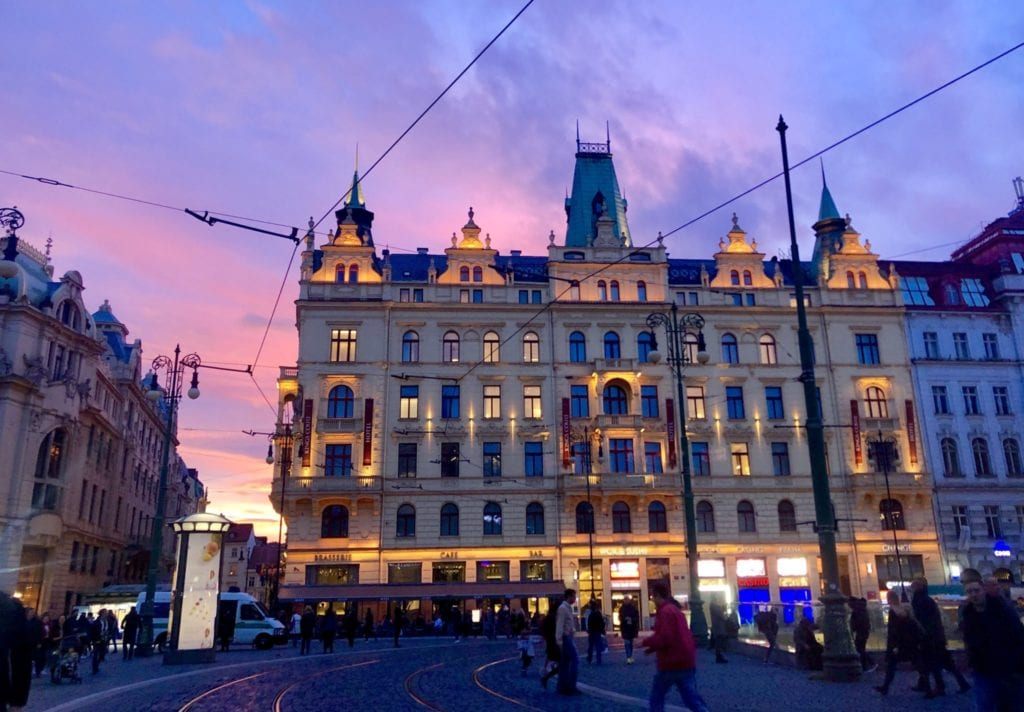 A fancy crenellated building in Prague with a bright pink and purple sunset behind it.