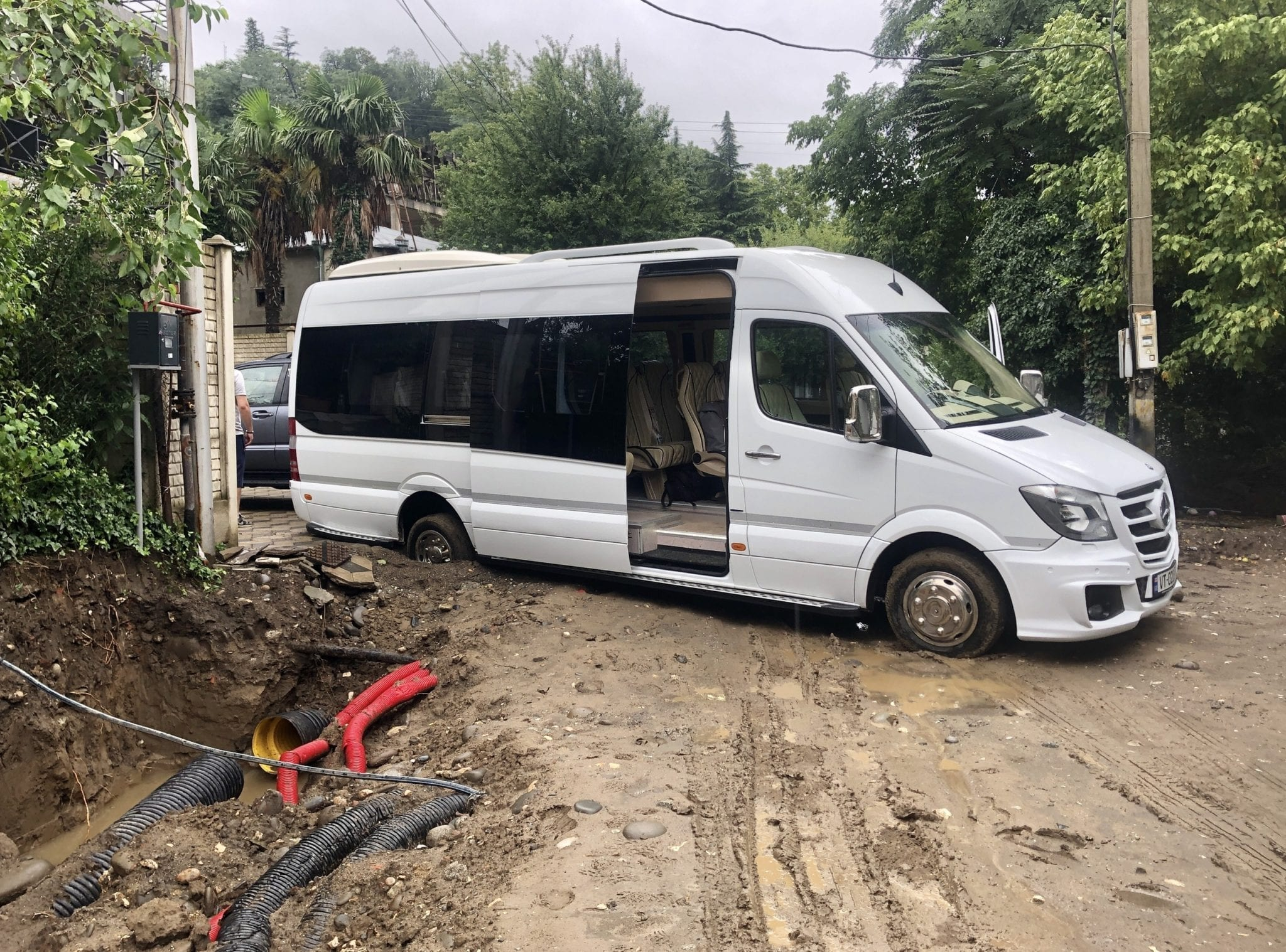 A white van on a torn-up muddy road, its back wheel sunken deeply into the mud.