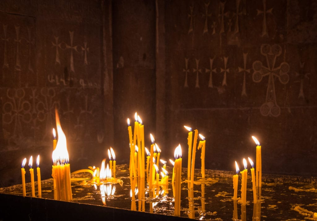 Candles lit on an altar inside a monastery in Armenia.
