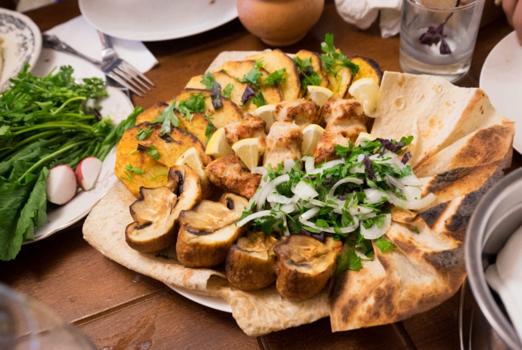 A plate full of Armenian bread, mushrooms, meat, and other mixed vegetables.