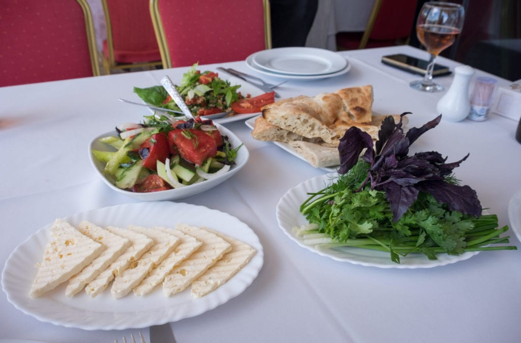 Armenian bread accoutrements: cheese, herbs, yogurt, and a salad of cucumbers and tomatoes.