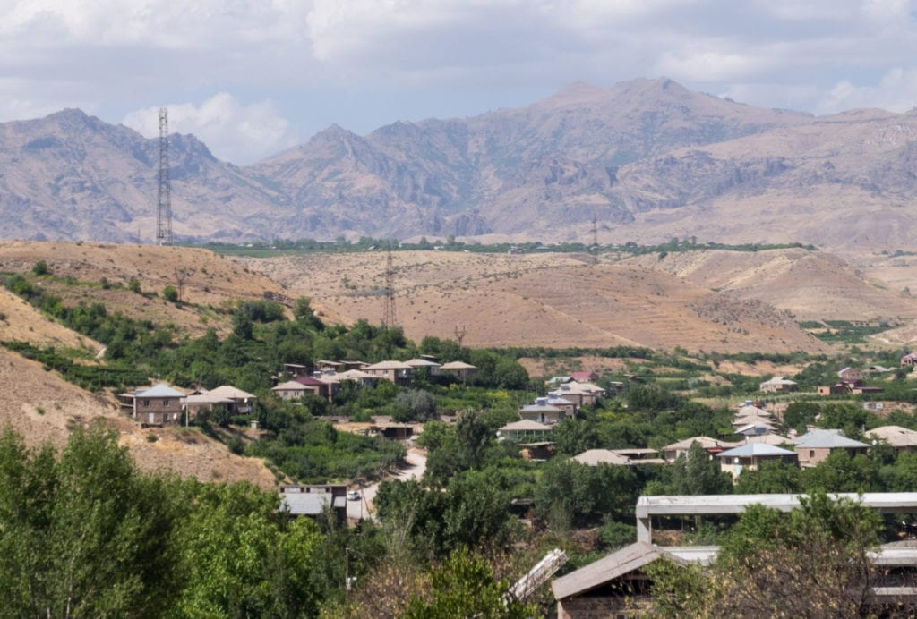 Green patches and homes in the Armenian desert, with mountains in the background.