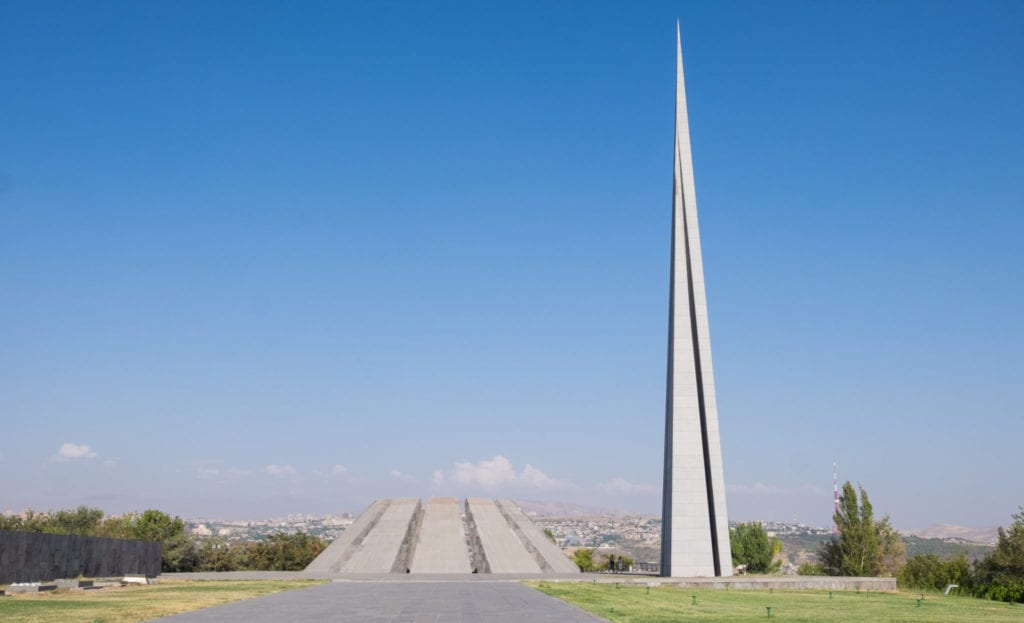 The trapezoid-shaped Armenian Genocide Memorial next to a tall, skinny tower.
