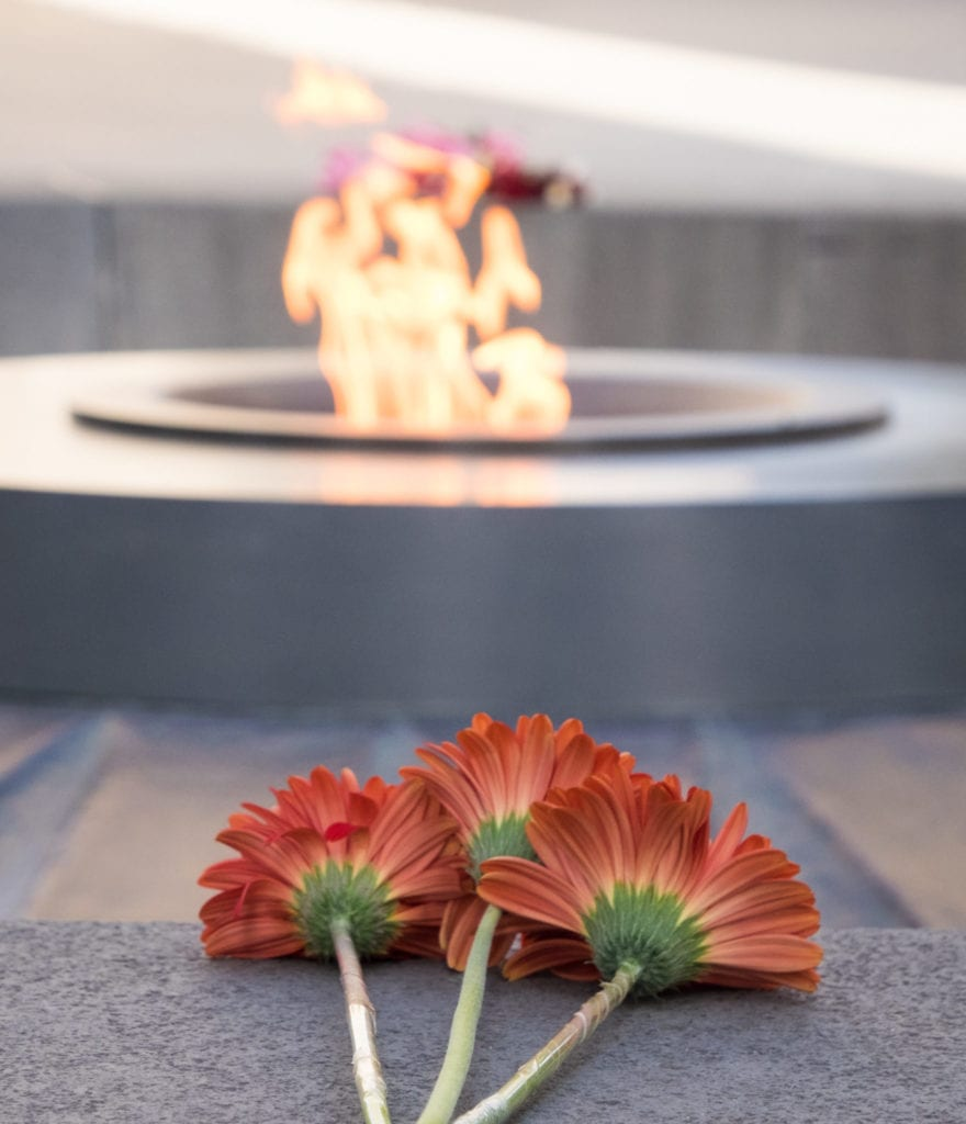 Three red flowers resting in front of the eternal flame at the Armenian Genocide Memorial.