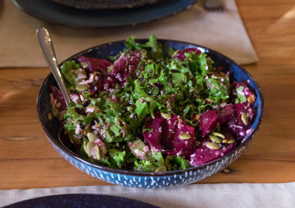 A salad with purple beets and lots of greens.