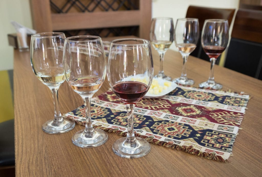 Six wine glasses surrounding a traditional Armenian patterned placemat.