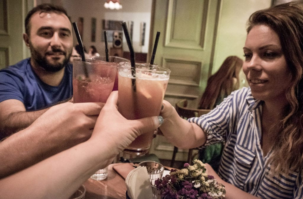Friends toasting four cocktails at a bar in Yerevan.