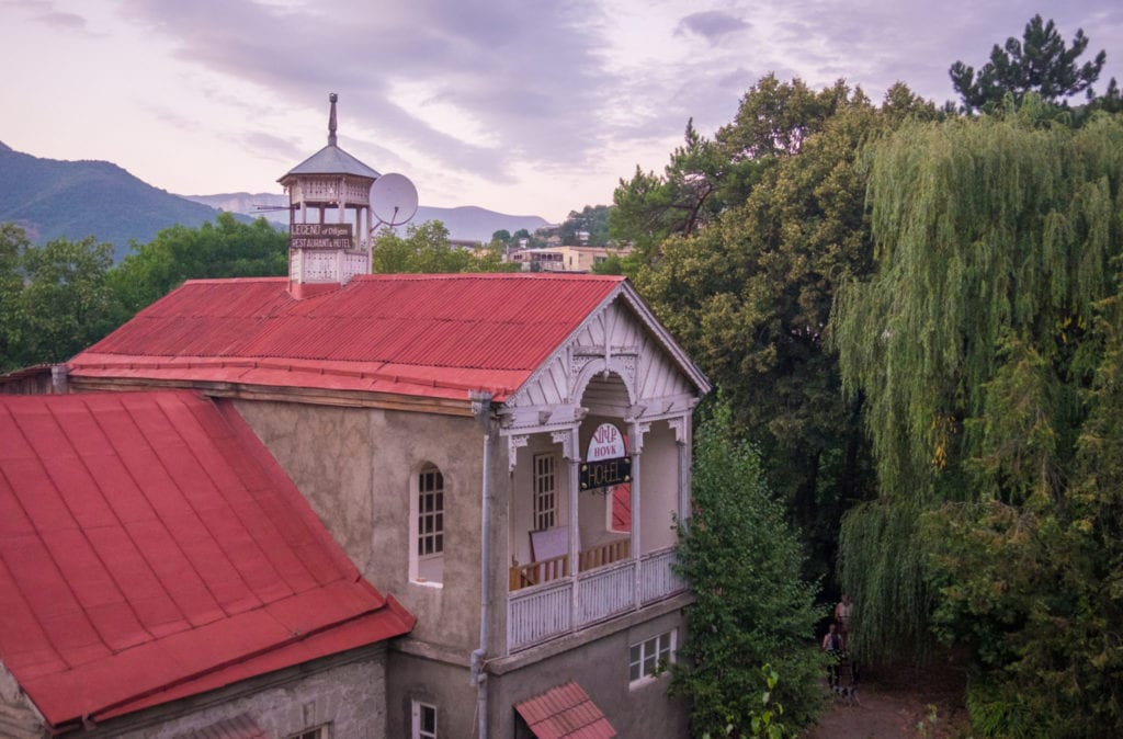 A church-like building with a red roof surrounded by weeping willow trees, under a dusky gray-lavender sky.