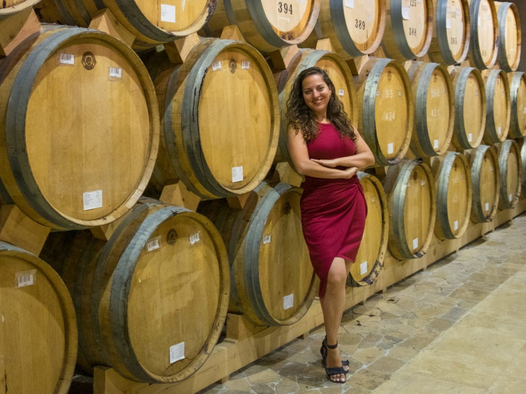Kate in a red dress standing in front of several barrels filled with Ararat brandy.