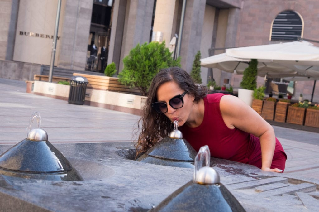 Kate leans down to drink from a pyramid-shaped water fountain in Yerevan, Armenia.