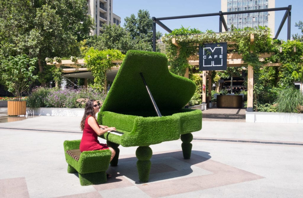 Kate plays a piano made of grass in Yerevan.