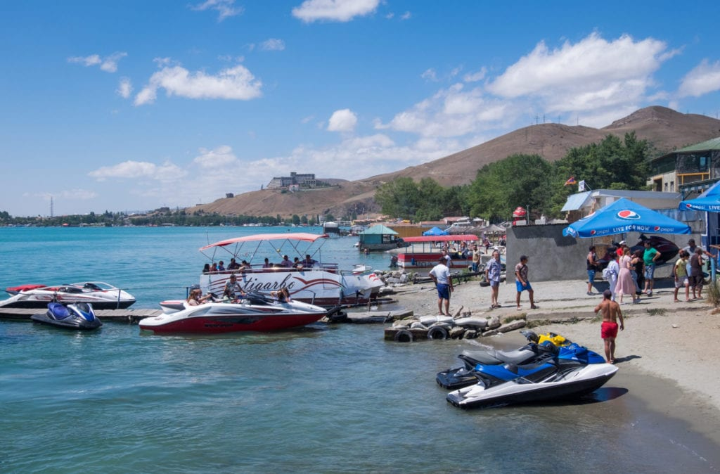Boats and docks along a beach on Lake Sevan in Armenia, mountains in the background underneath blue sky.