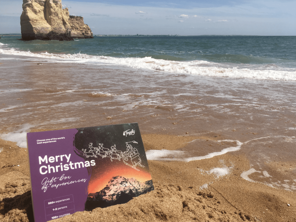 """A Tinggly gift card reading """"Merry Christmas"""" on the beach, next to the water."""
