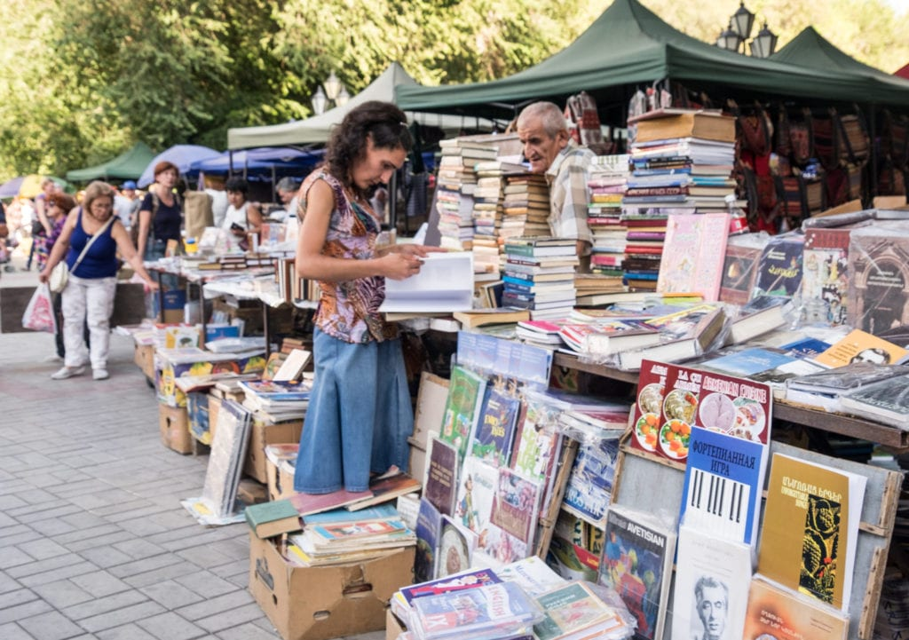 A woman peruses books on a table at an outdoor market in Yerevan.
