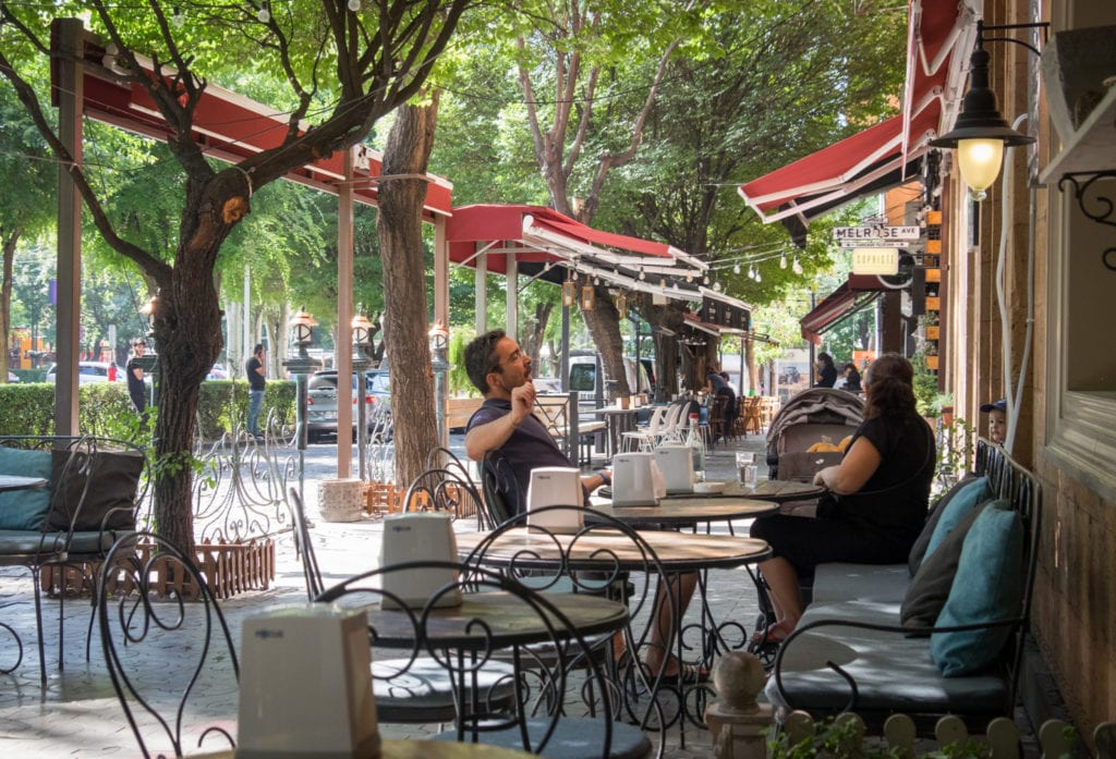 A couple sitting at an outdoor cafe in Yerevan, surrounded by leafy trees.