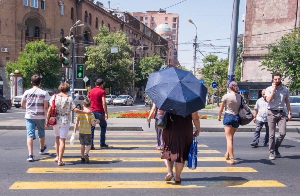 People walking across a yellow crosswalk on a street in Yerevan.