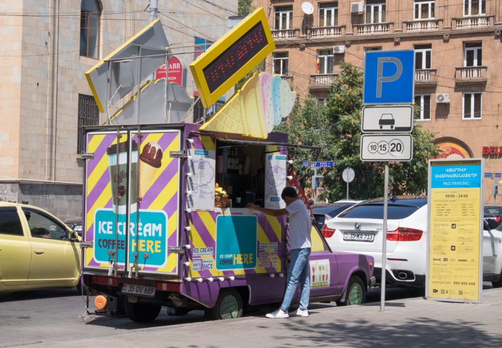 A man ordering from a yellow and purple-striped food truck on a street in Yerevan.