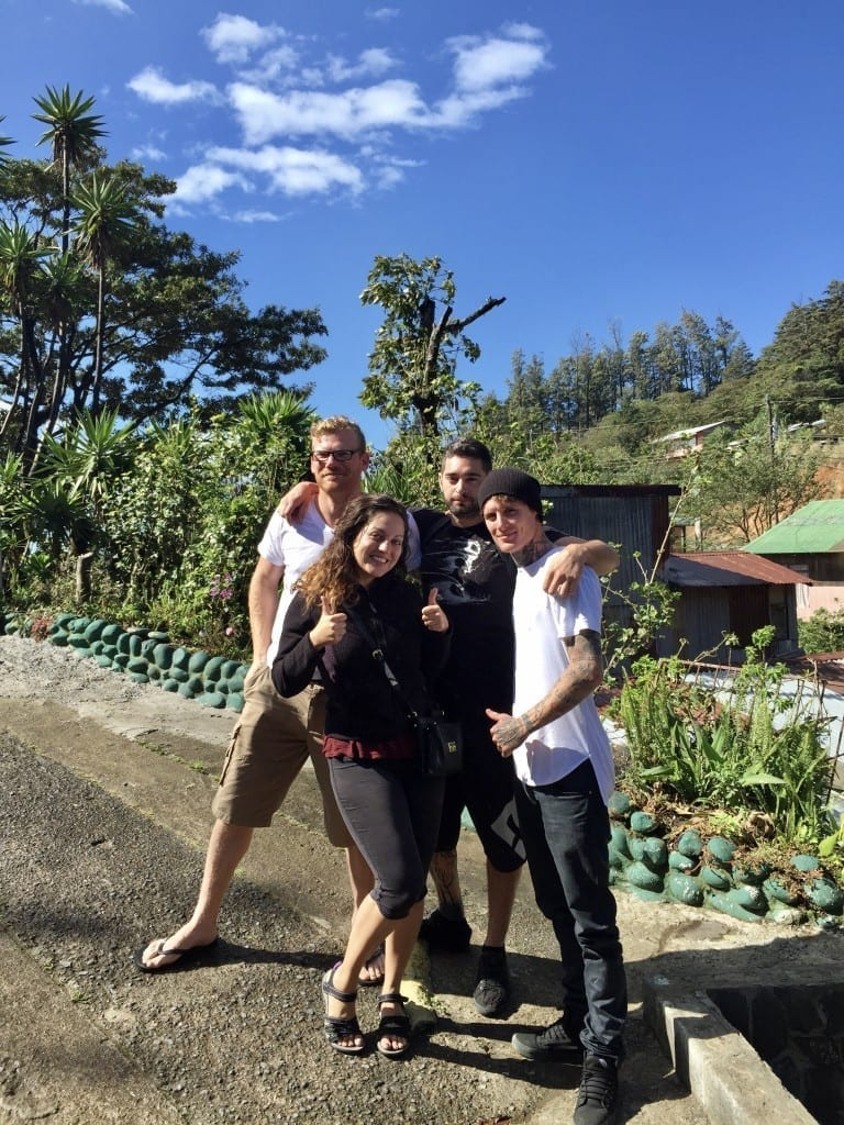 Kate posing with three guy friends on a Costa Rican road, trees and vegetation in the background.