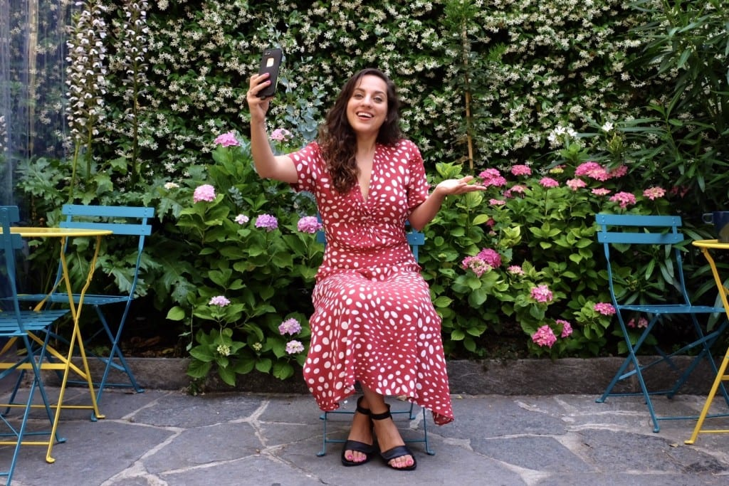 Kate wears a red and white polka-dot dress and attempts to take a selfie in a garden.