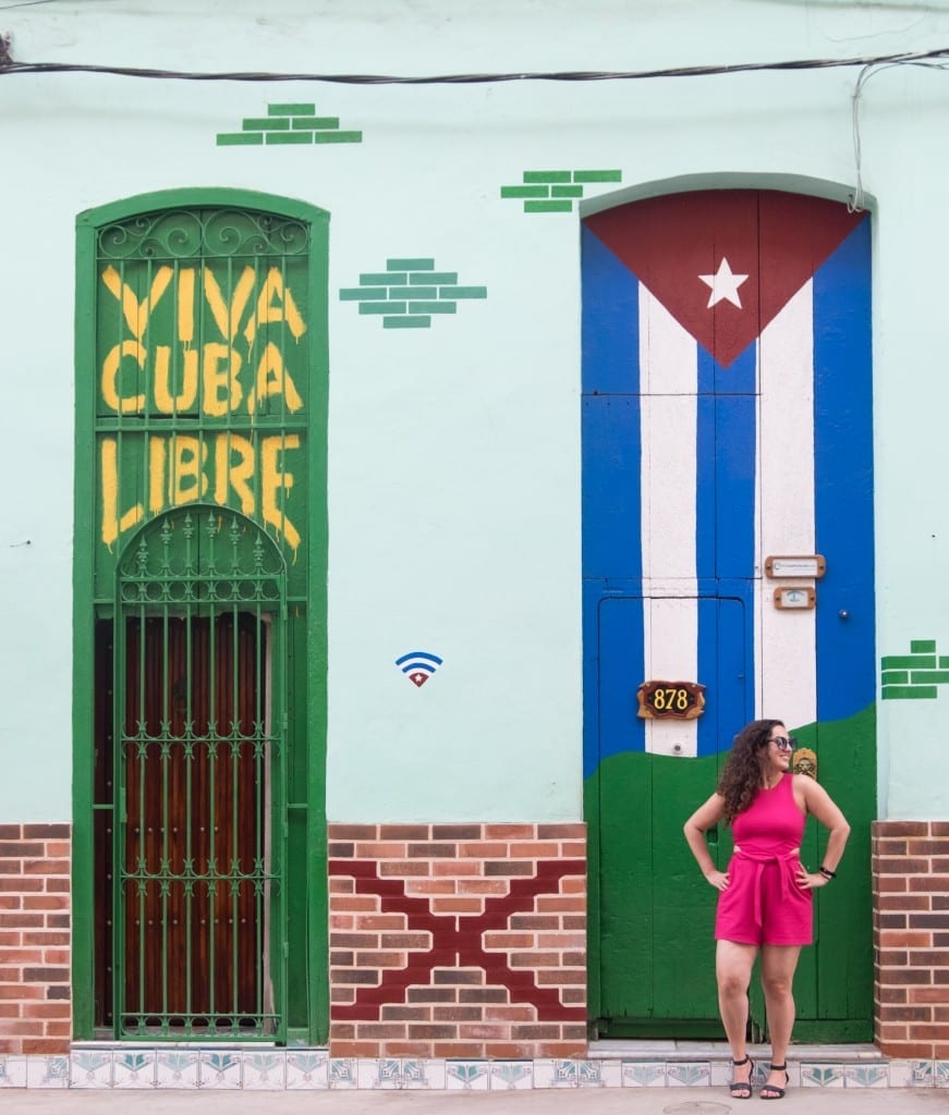 """Kate stands in front of a mural in Cuba reading """"Viva Cuba Libre"""" with a Cuban flag."""
