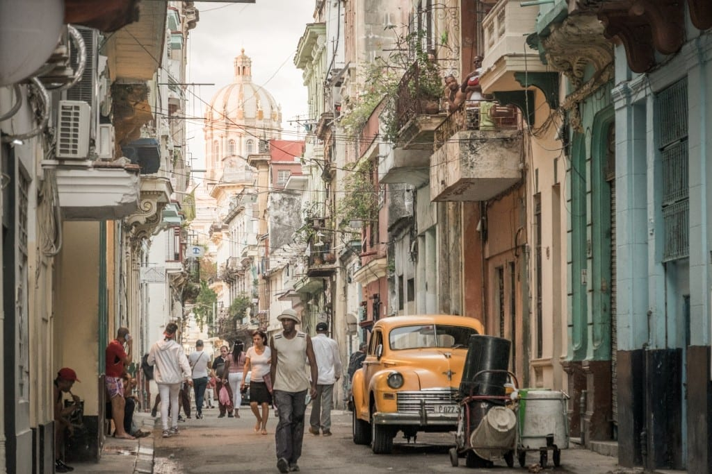 Chaotic Havana streets filled with people, a yellow car, and a church tower in the background.