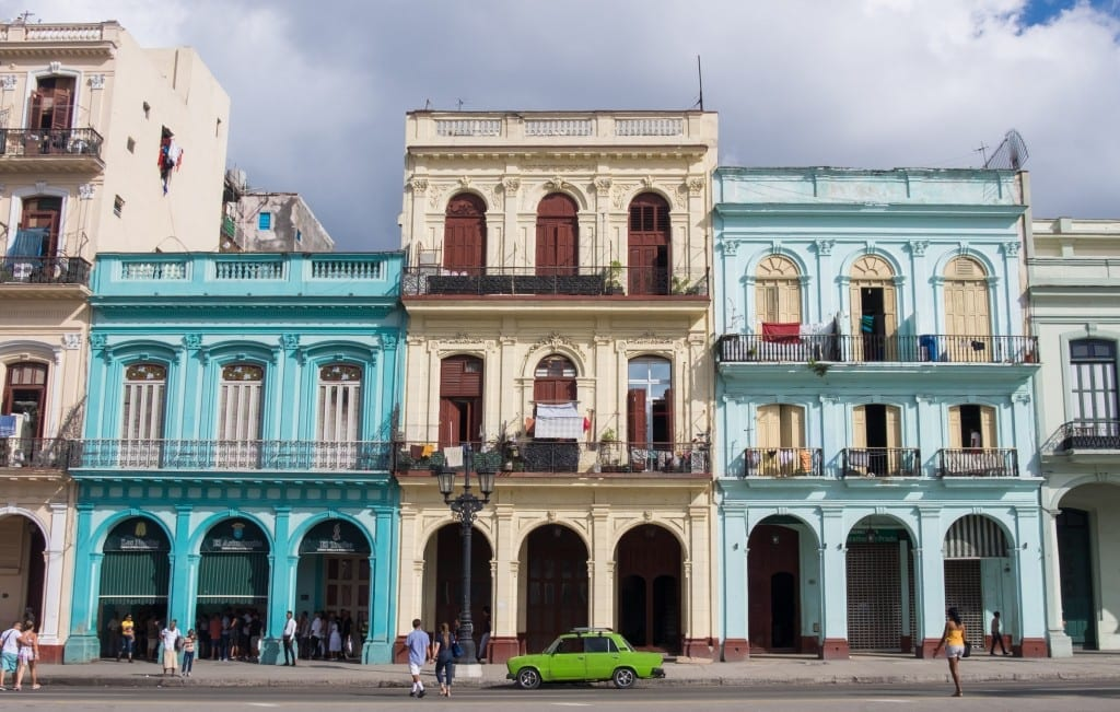 A bright green car in front of blue and white colonial homes in Havana.